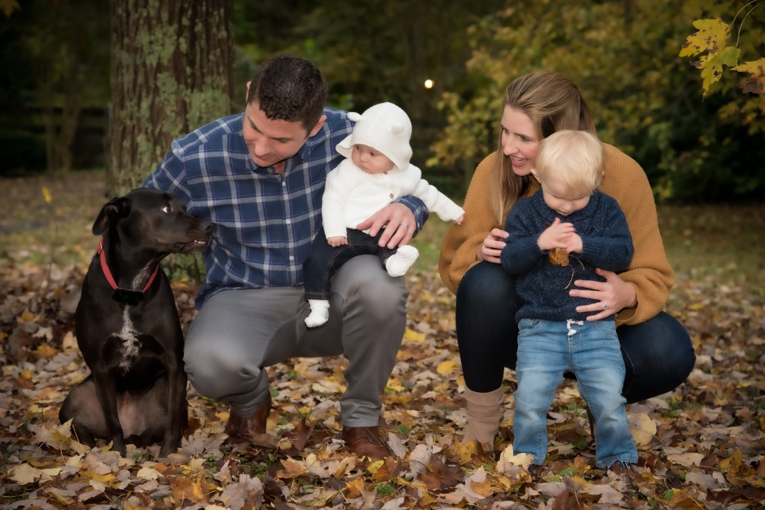 A family of two adults, two children and a dog are shown in a bed of yellow, Fall leaves. From left to right: black medium sized dog with red collar and white strip on her chest; a father wearing a blue plaid shirt and gray pants holding his baby daughter (4 months old) wearing a white hooded sweater, jeans and white socks; mother is crouched down wearing a gold sweater, blondish brown hair, jeans and short tan boots is behind her 2-year old son who has blond hair, wearing a blue cable sweater, light denim jeans and holding a leaf. The boy's head is down. The mother, father and baby look at the dog and he looks back.