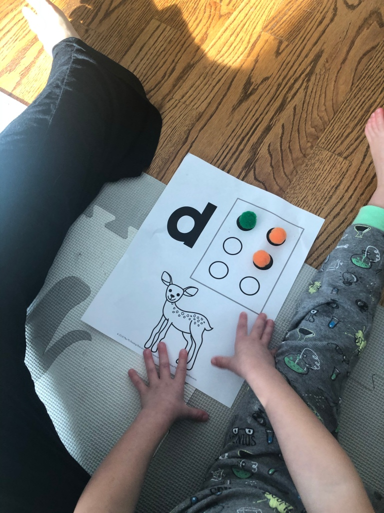 A white piece of paper with a drawing of a deer, the letter d and then three pom pom balls in the shape for the Brailled letter of d. Little boy has two hands on the paper.