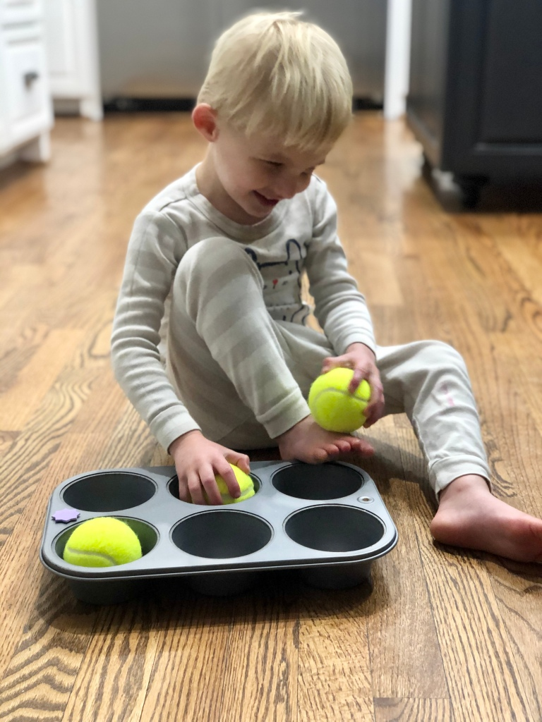 Little boy sitting on the kitchen floor with one hand holding a tennis ball. The other hand rests on a ball inside of a muffin tin. There is a third ball in the tin as well.